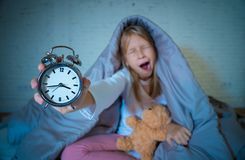 Girl sitting on bed awake in the middle of the night yawning and feeling restless with insomnia. Cute sleepless little girl sitting on bed showing alarm clock stock photography