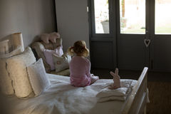 Girl sitting on bed in the bedroom at home stock images