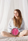 Girl is sitting on bed with big pink clock. 6 a.m Royalty Free Stock Image