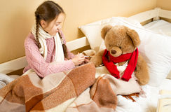 Girl sitting on bed and doing injection to brown teddy bear Stock Images