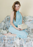Girl sitting on bed giftbox in hands Stock Photography