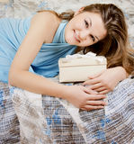 Girl sitting on bed giftbox in hands Stock Images