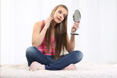 Girl sitting on the bed and holding a mirror. Young long-haired blonde sitting on the bed and looks at the mirror Stock Photography
