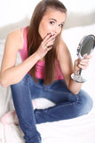 Girl sitting on the bed and holding a mirror Royalty Free Stock Photo