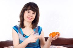 Girl sitting on the bed and keeps mandarins Stock Images
