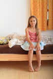 Girl sitting on bed. Little girl - barefoot child sitting on bed and going to sleep Stock Image