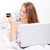 Girl sitting in bed and shopping online with credit card Stock Photos