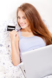 Girl sitting in bed and shopping online with credit card Royalty Free Stock Photography