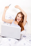 Girl sitting in bed and shopping online with credit card Royalty Free Stock Images