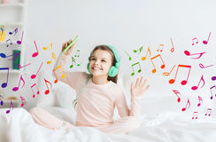 Girl sitting on bed with smartphone and headphones Royalty Free Stock Image