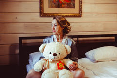 Girl sitting on bed with soft toy. Portrait of cute young girl who is sitting on the bed in his room and holds a soft toy in the hands and smiling Stock Photo