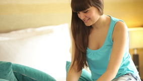 Girl sitting on bed and typing with smile stock footage