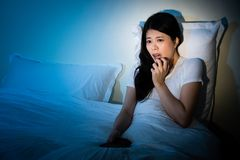 Girl sitting on bed watching tv a scary movie Stock Photo