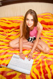Girl sitting in the bedroom on the bed with laptop Royalty Free Stock Photo