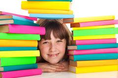 Girl sitting behind pile of books Stock Photography