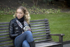 Girl sitting on the bench Stock Images