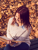 Girl sitting on bench in ark and reading a book. Happy redhead girl sitting,smiling and reading a book on bench in park Stock Images