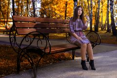 Girl sitting on a bench in the autumn Park stock photo