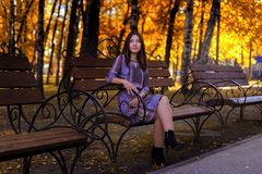Girl sitting on a bench in the autumn Park royalty free stock photos