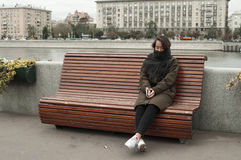 Girl sitting on the bench. On the bank of Moscow-river stock photography