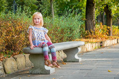 Girl sitting on bench in city park Stock Photography