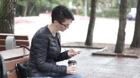 Girl with a smartphone. A girl is sitting on a bench with coffee and writing a message in a smartphone stock video footage