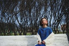 Girl sitting on a bench face exposed to the sun. Brunette girl sitting on a bench face exposed to the sun Stock Images