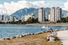 Girl Sitting on a Bench in front of Downtown Vancouver, Canada Stock Photography
