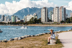 Girl Sitting on a Bench in front of Downtown Vancouver, Canada stock photo