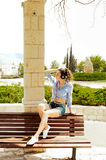 Girl sitting on a bench and listening to music Royalty Free Stock Photos