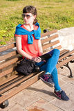 Girl sitting on a bench near the sea Stock Photos