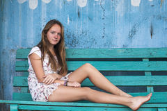 Girl sitting on the bench, old dirty wall on the background. Young girl sitting on the bench, old dirty wall on the background Stock Image