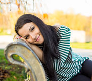 Girl sitting on bench outdoors Royalty Free Stock Photography