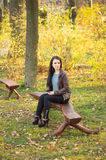Girl sitting on bench outdoors Stock Image
