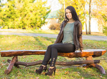 Girl sitting on bench outdoors Stock Photography