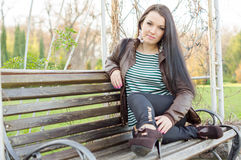 Girl sitting on bench outdoors Royalty Free Stock Photos