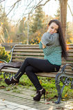 Girl sitting on bench outdoors Stock Photos