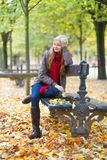 Girl sitting on a bench in park on a fall day Royalty Free Stock Photos