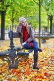 Girl sitting on a bench in park on a fall day Royalty Free Stock Photography