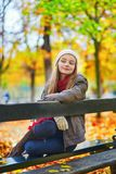 Girl sitting on a bench in park on a fall day Stock Photos