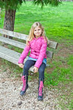 Girl sitting on a bench in the park Stock Images