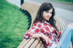 Girl sitting on a bench. Girl in a plaid shirt sitting on a bench Royalty Free Stock Photo