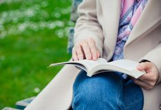 Girl reading on a bench stock images