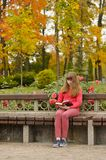 Girl is sitting on bench and reading book,  autumn. Young girl is sitting on bench and reading book, outdoors, autumn Royalty Free Stock Images
