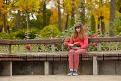 Girl is sitting on bench and reading book, autumn. stock images