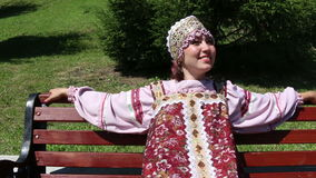 Girl sitting on a bench, Russian folk costume stock footage