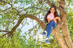 Girl sitting on the bench of tree in forest alone Stock Photo