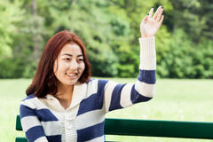 Girl sitting on bench, waving hand Stock Photos