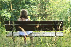 Girl sitting on a bench Stock Image