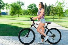 Girl sitting on bicycle Stock Photos